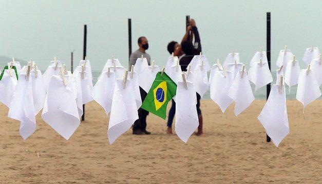 Ato em memória dos quase 600 mil mortos pela Covid no Brasil estende lenços brancos em Copacabana