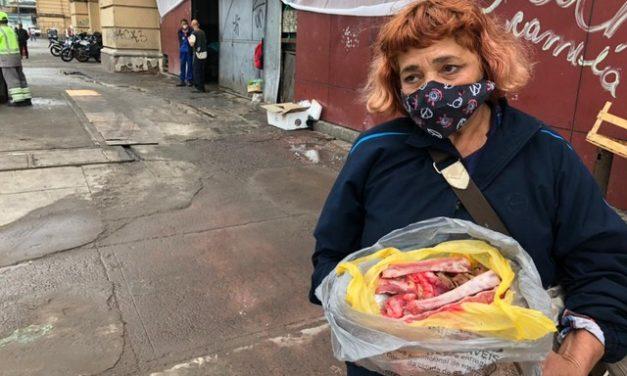 Pessoas buscam ossos de carne na caçamba de descarte do Mercadão, Centro de SP
